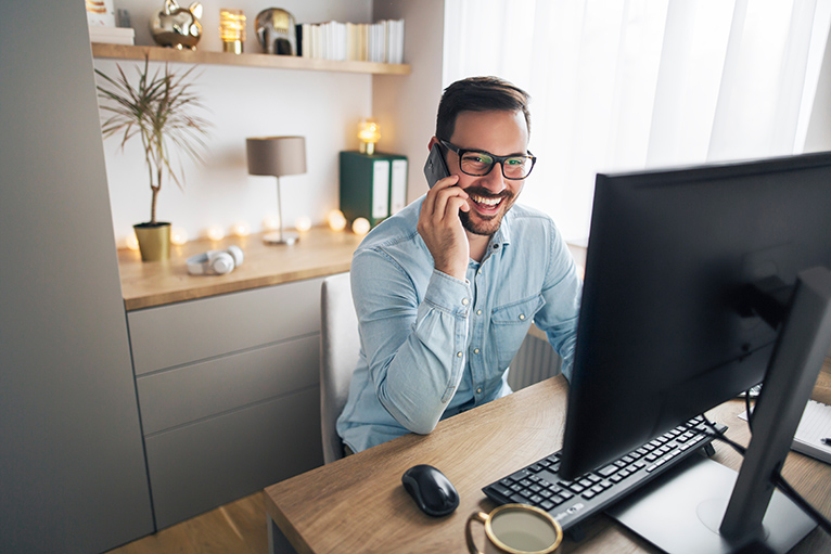 Smiling man using mobile phone in office space with lamps, fairly lights and ornaments on shelves in the background