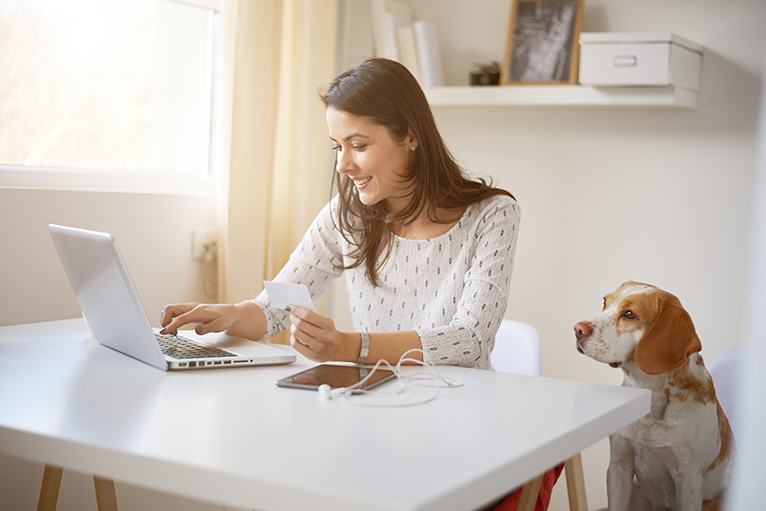 Young woman using laptop in home office with floating shelf behind her and her dog sat next to her