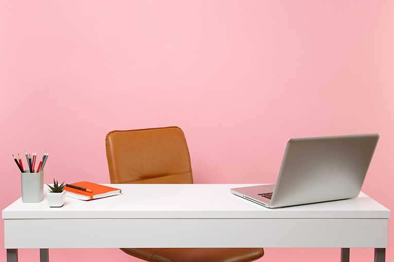 Desk in front of pink wall in home office