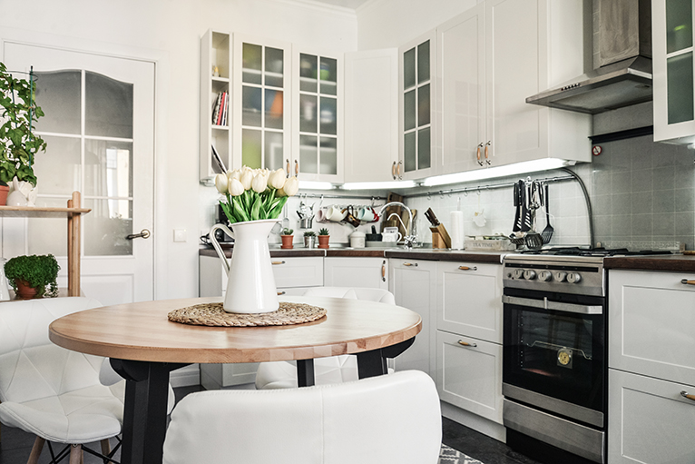 Bright white kitchen with lilies on the table