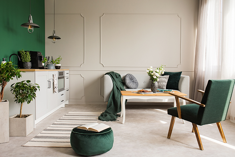Open plan kitchen with green design accents, including a pouffe, blanket and cushions