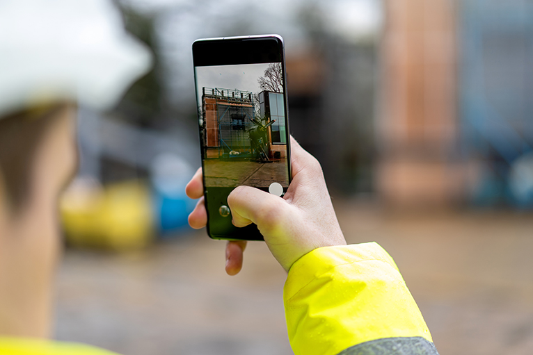 Tradesperson taking a picture on site using a smartphone