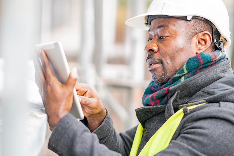 Trades technology: Tradesman using a tablet on site