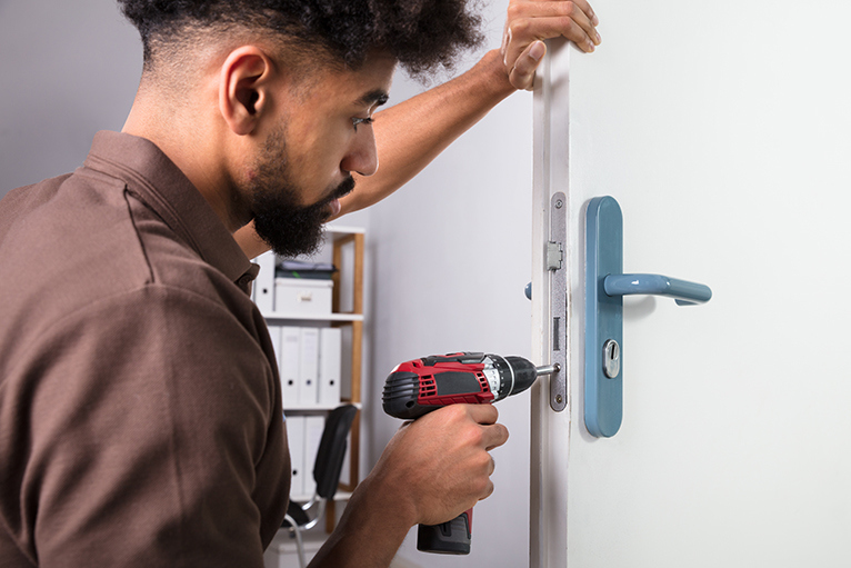 Home security: Locksmith installing a lock