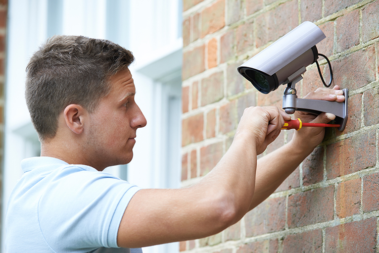 Security specialist installing a home security camera on the outside of a house