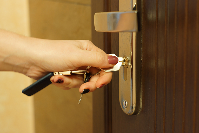 Home security: Person unlocking a door with a key