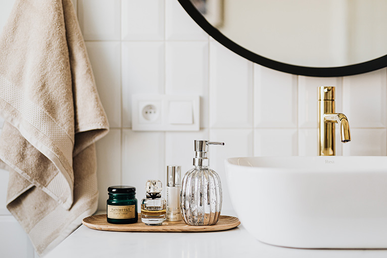 2021 home improvements: White bathroom sink and gold tap next to skincare products