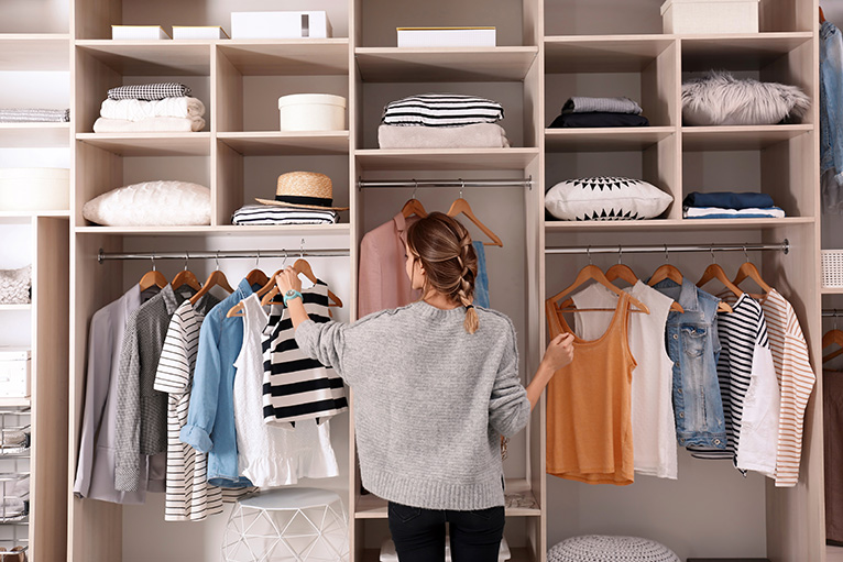 Person choosing clothing from wall mounted wardrobe