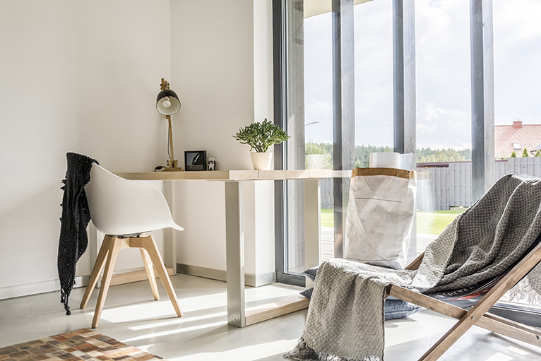Desk and indoor deckchair placed in front of bright wall-to-ceiling windows