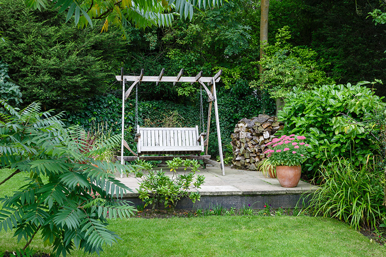 Garden swing on raised platform in garden