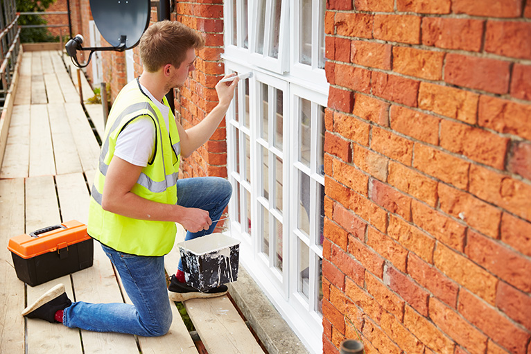 Painter painting external window frames with white paint