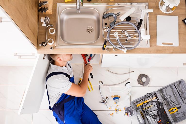 Plumber working under a sink