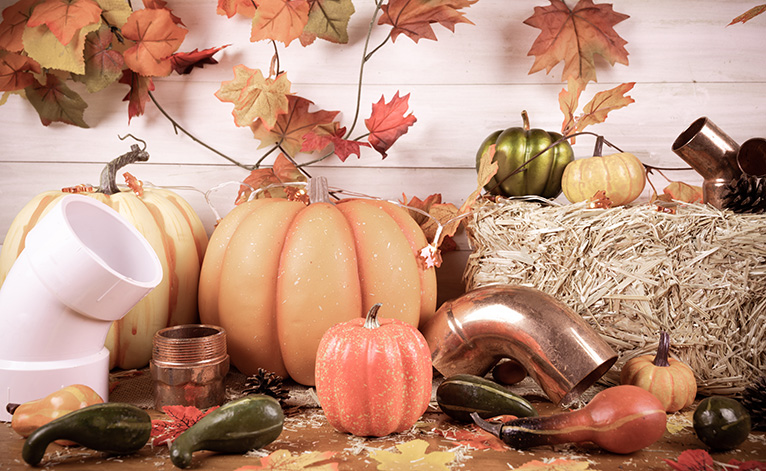 Decorative pumpkins next to parts of pipe