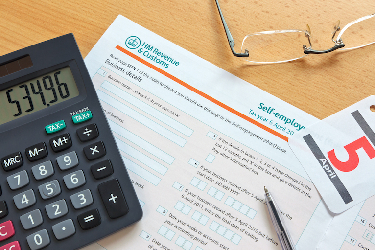 Self-assessment tax form, calculator and glasses on a table
