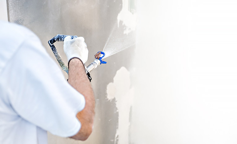 Painter spraying paint onto a wall