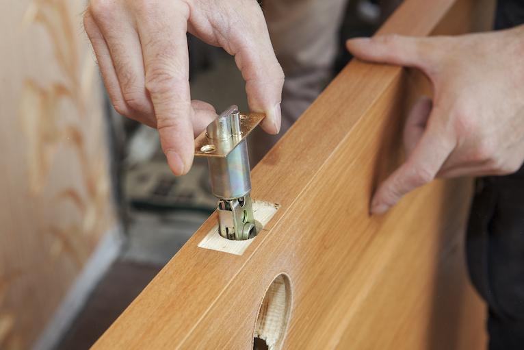 Locksmith installing lock in door