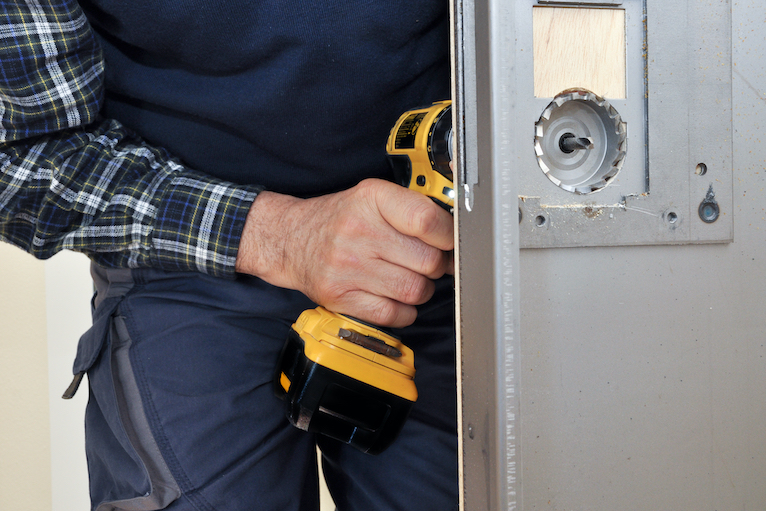 Locksmith using a drill
