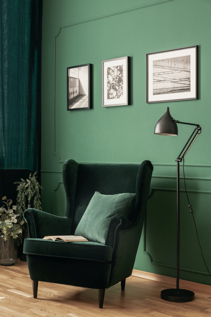 Home design: Dark green velvet chair in front of lighter green wall