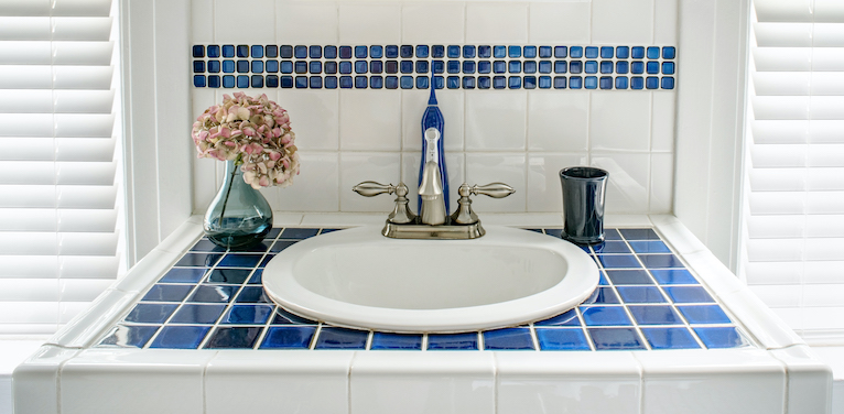 Sink surrounded by blue and white tiles