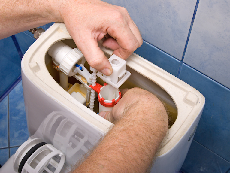 Plumbing problems: Person fixing issues inside toilet cistern