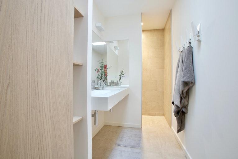 Peg-style bathroom wall hooks holding towels