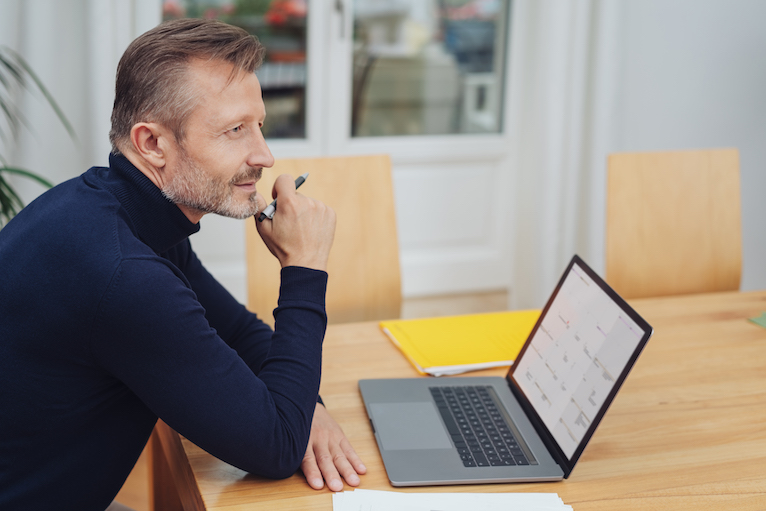 Person thinking and looking at laptop