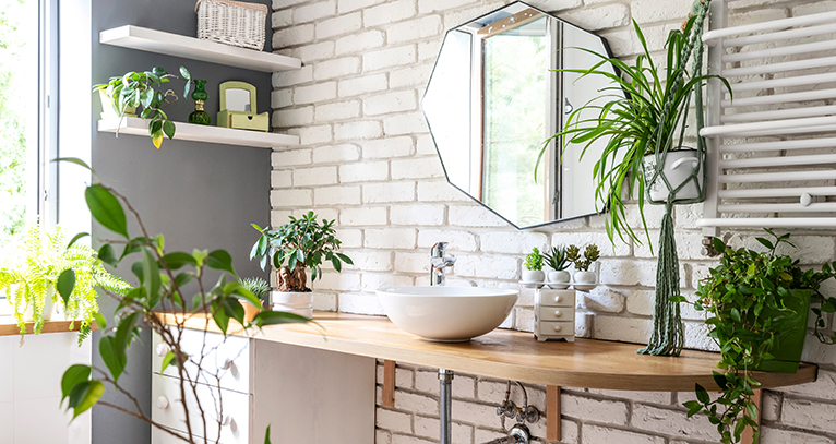 Bathroom with lots of plants and white brick wall