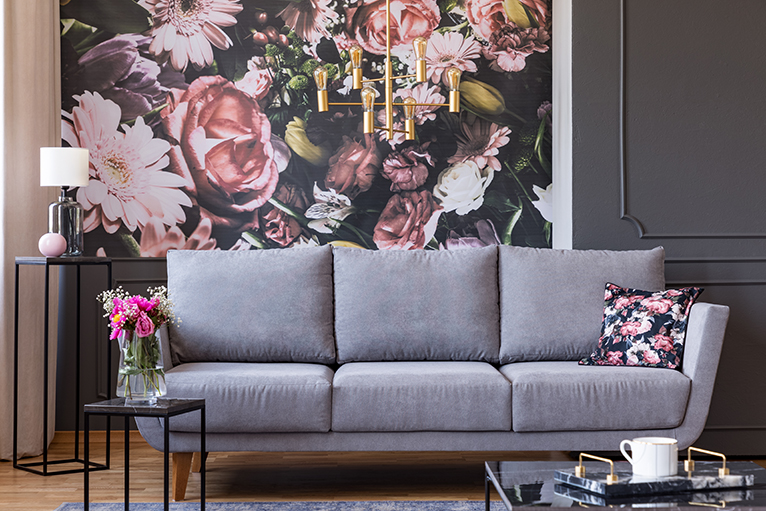 Grey sofa in front of floral feature wall