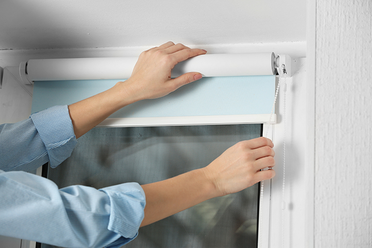 Person's hands installing blinds with baby blue lining