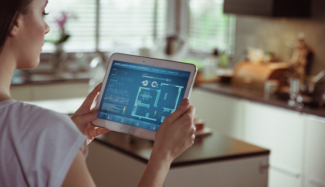 Woman using intelligent home controls software on a tablet to set the right temperature for each room.