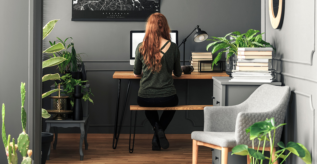 Young woman working on a computer in a home office surrounded by green houseplants.