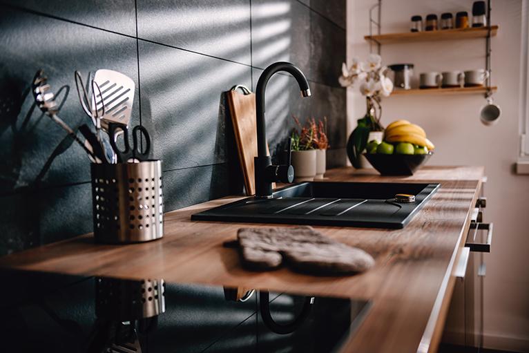 Kitchen with black taps, sink and tiled splashback
