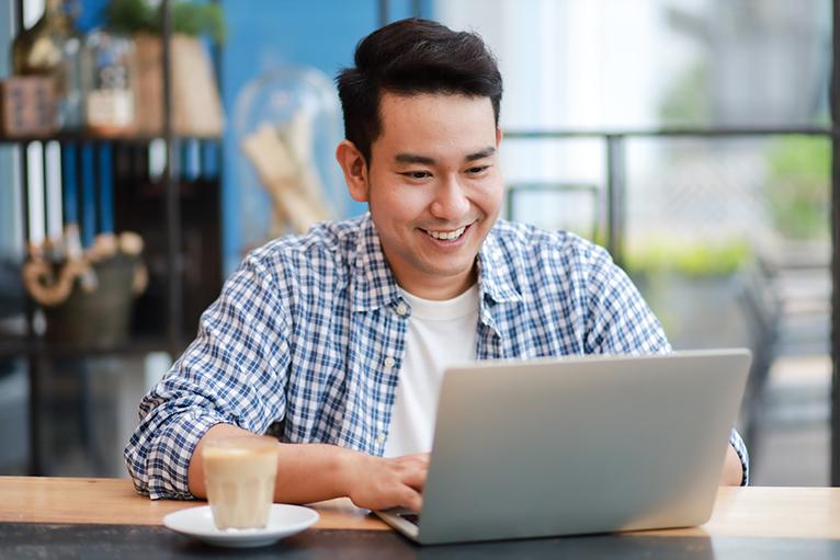 Money saving tips: Man using laptop in coffee shop