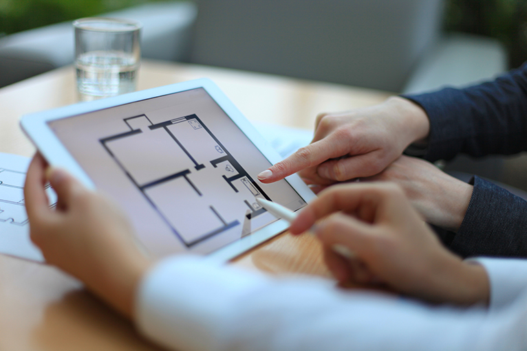 Estate agent showing house plans on a tablet