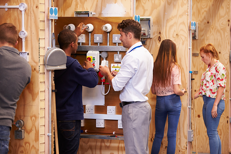 Trades training: Teacher helping trainee electricians