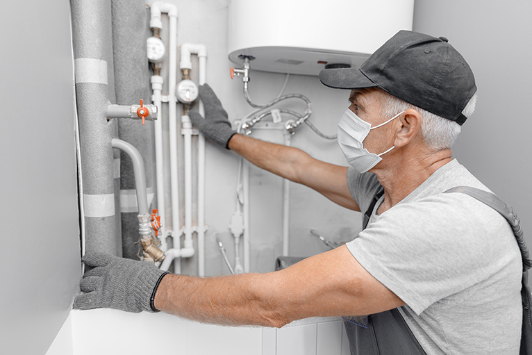 Plumber wearing mask in home, looking at pipes