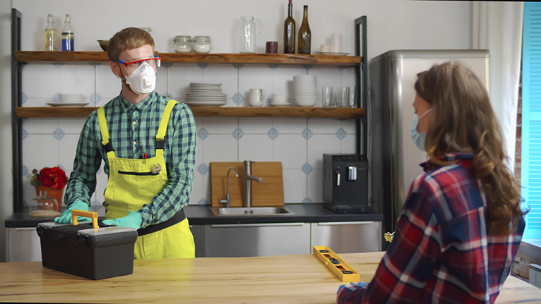 Tradesperson in home wearing mask, talking to homeowner