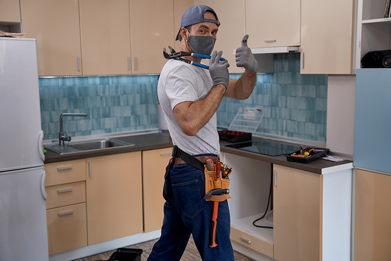 Tradespeople: Kitchen fitter wearing mask and giving a thumbs up to the camera