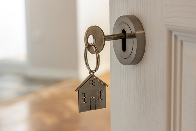 Key with house-shaped keyring in the door to a new home