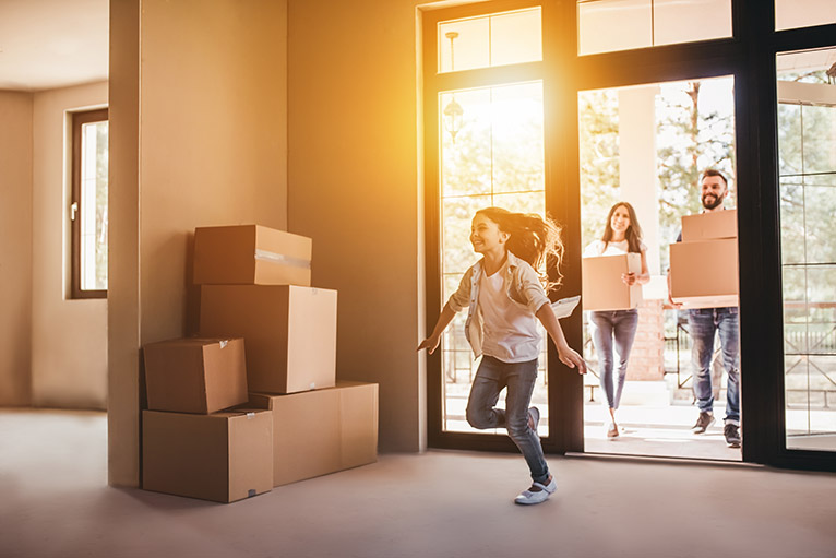 Stamp duty extension: Smiling family carrying boxes into new home
