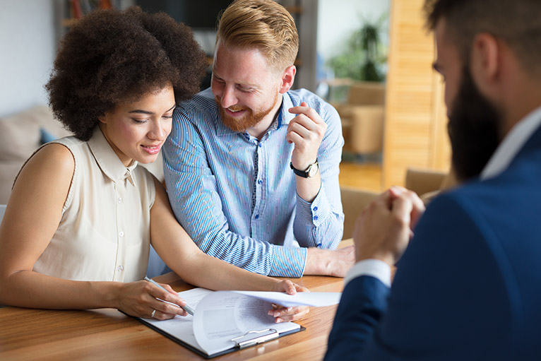 Mortgage guarantee scheme: Smiling couple looking at mortgage documents