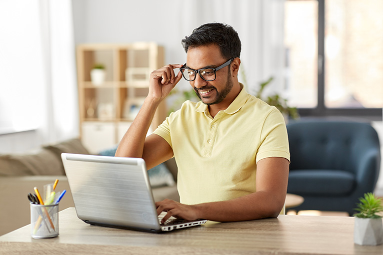 Person smiling and looking at laptop