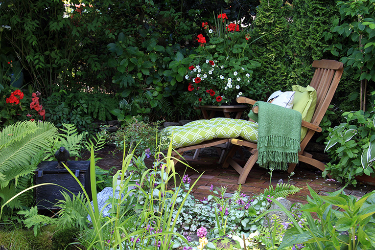 Lounge chair in garden with lots of plants
