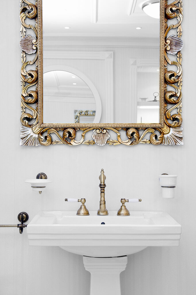 Carved gilded mirror above bathroom sink