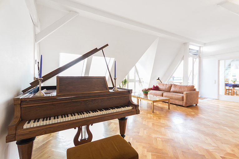 Baby grand piano in open plan room
