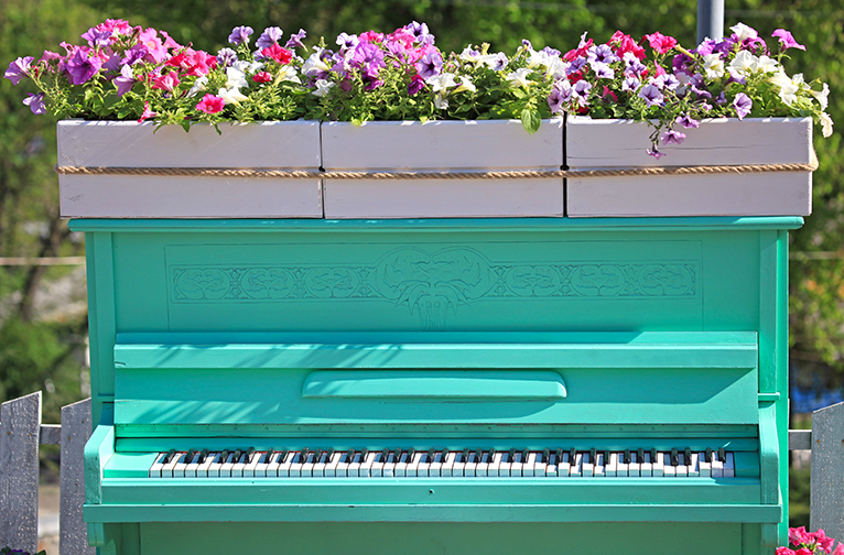 Teal piano with flower planters on top in garden