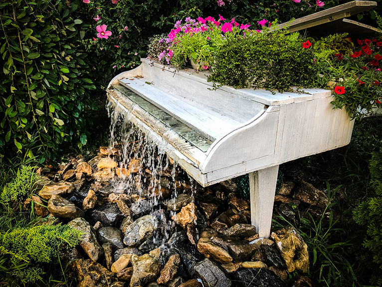 Hollowed out grand piano in garden with plants and water feature