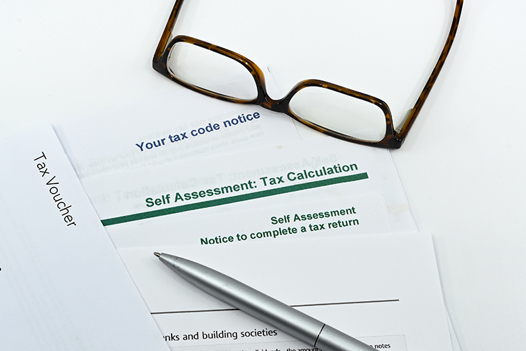 Tax documents, pen and glasses on table