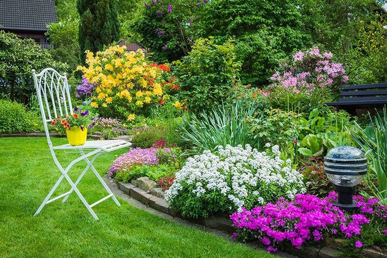Garden with blooming flowerbeds and decorative garden chair
