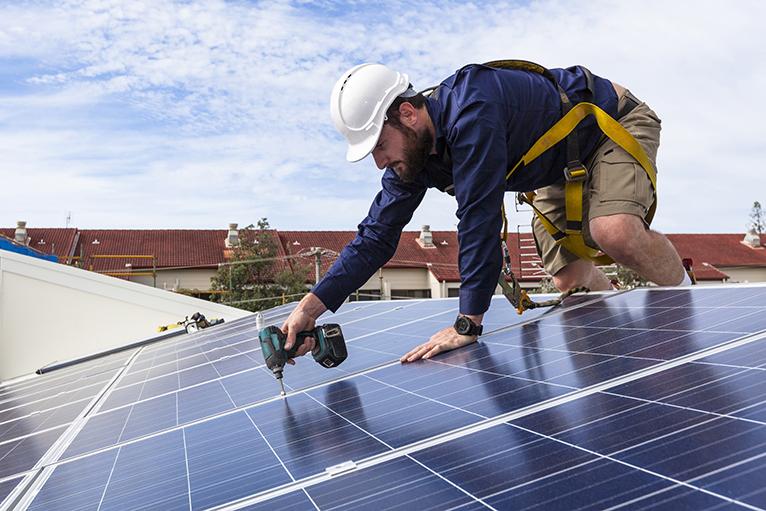 Solar panel installer working on roof